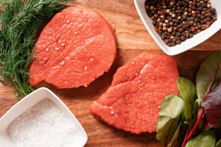 Raw beef steaks on wooden table. Herbs, salt on wooden background. Flat lay top view Stock Photo