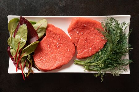 raw steak dinner of two beef steaks herbs vegetables. Flat lay top view, rustic metal background