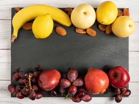 fruits background red and yellow color set on dark stone slake plate and white wood table. Summer abstract creative trendy fresh health concept. Flat lay top view copy space.