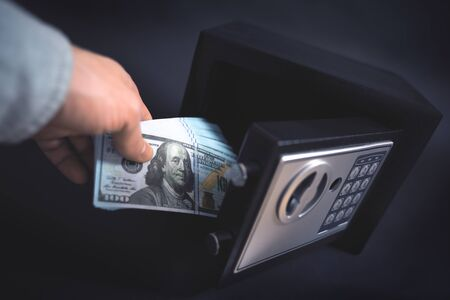 Cash Money Safe Deposit. Symbol of money safety. The man puts a wad of dollars in small Residential Vault. Toned soft focus picture. 版權商用圖片
