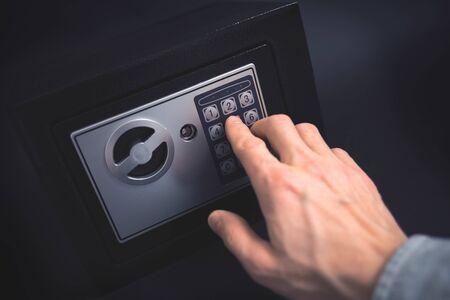 Cash Money Safe Deposit. Symbol of money safety. Man open small Residential Vault. Toned soft focus picture. 版權商用圖片