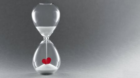Hourglass on dark background. Symbol of Time for love. Concept passing love.