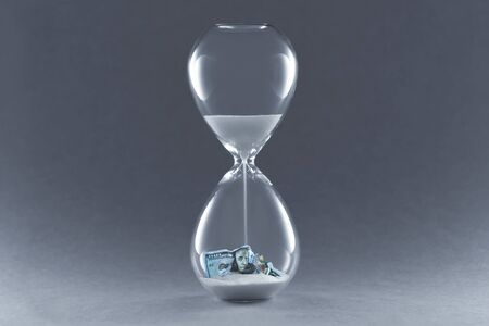 Hourglass on dark background. Concept passing traditional currency time. End of dollar currency.