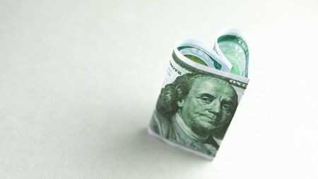 dollar bill in form of heart - as symbol of love, success and wealth. Copy space.