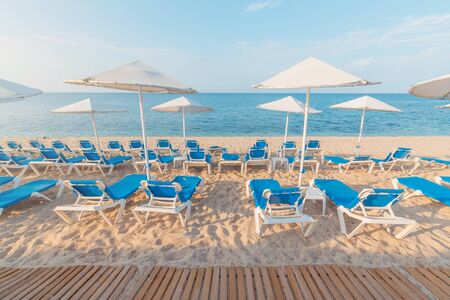 Low season empty beach with sun loungers and straw umbrellas. in Crete town Hersonissos Day foto. Greece vacation. Banco de Imagens