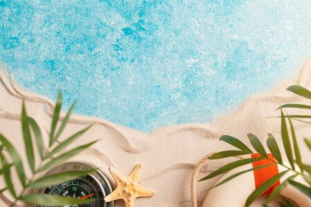 vacation and travel concept, Flat lay top view copy space, Minimal exotic concept. layout of sand waves and sea, summer beach background with shell, sea star, compass life preserver and blurred Palm