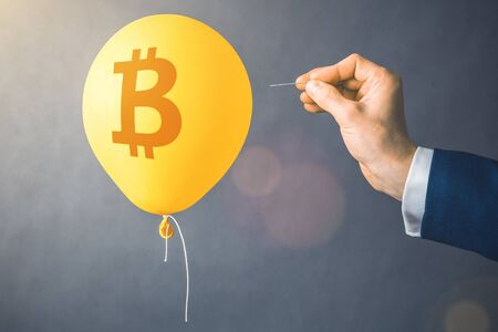 Bitcoin cryptocurrency symbol on yellow balloon. Man hold needle directed to air balloon. Concept of finance risk.