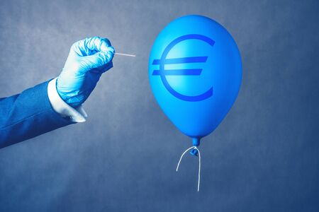 Euro currency symbol on blue balloon in coronavirus time. Man hold needle directed to air balloon. Concept of finance risk.