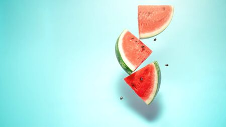 Watermelon slice falling on pastel background. Floating fruits in the air. Flying red fruits. Summer background. Trend colors, copy space.