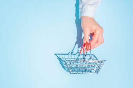 hand holding empty metal shopping basket. Concept of consumerism, shopping symbol. Copy space trend pastel color. Hard shadows, morning light. 版權商用圖片