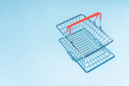 Empty metal shopping basket. Concept of consumerism, shopping symbol. Copy space trend pastel color. Hard shadows, morning light.
