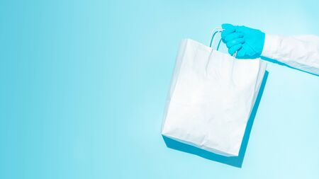hand in gloves holding shopping paper bag. Concept of consumerism, shopping symbol during pandemic time. Copy space trend pastel color. Hard shadows, morning light.