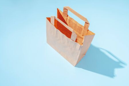 Shopping paper bag. Concept of consumerism, shopping symbol. Copy space trend pastel color. Hard shadows, morning light. 版權商用圖片