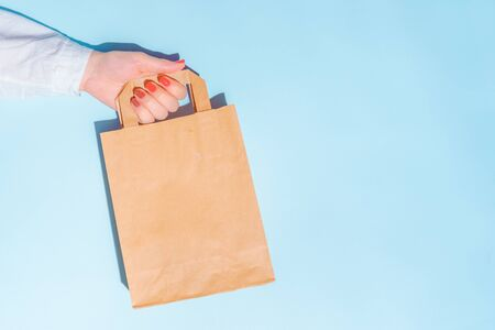 hand holding shopping paper bag. Concept of consumerism, shopping symbol. Copy space trend pastel color. Hard shadows, morning light.