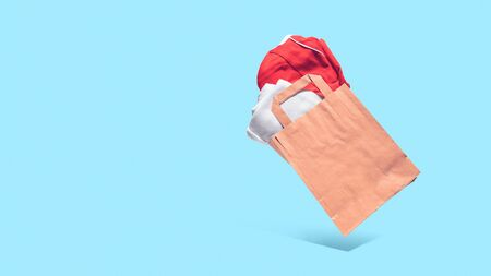 Flying shopping paper bag with purchases. Concept of consumerism, ease of shopping. Copy space trend pastel colors.