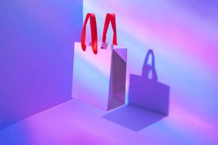 Flying shopping paper bag in neon light. Concept of consumerism, ease of shopping. Copy space trend pastel colors.