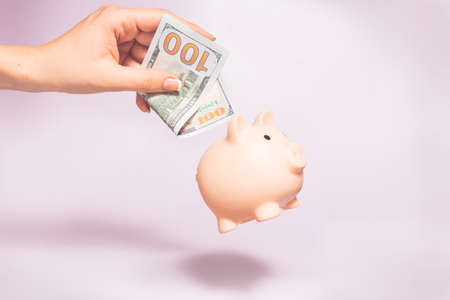 Money holding concept. Saving symbol - Close-up Of A woman Hand puts a 100 dollar bill in Pink Piggy Bank. Money box on a pastel background. Copy space.