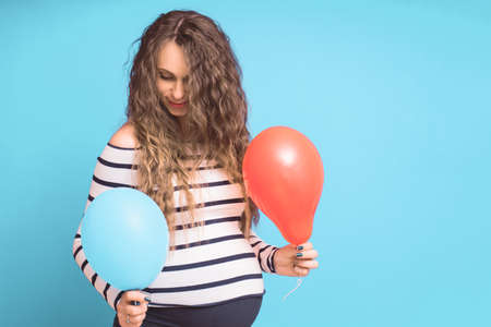 Pregnant woman tries to guess the boy or girl. Balloons as symbol of boy and girl. Gender of the unborn child concept. Copy space.
