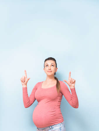 Young beautiful pregnant woman over isolated blue background pointing fingers up, showing product. Presenting your product. Copy space