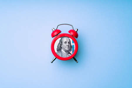 US dollar bill in alarm clock. Concept of deadline to invest. Time is money idea. Time to making money. Banque d'images