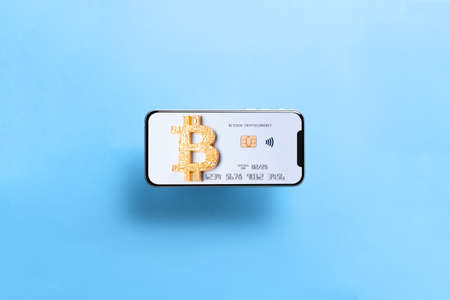 Smartphone with bitcoin card. New black frameless hovering smartphone with Bitcoin paying symbol. Bank bitcoin cryptocurrency card as shopping and trading concept. 版權商用圖片