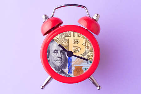Bitcoin and US dollar bill in alarm clock. Concept of deadline to invest in cryptocurrency. Time to invest in bitcoin idea. 版權商用圖片