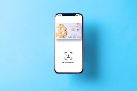Bitcoin paying symbol. Bank bitcoin cryptocurrency card in hovering smartphone screen. Shopping and trading bitcoin concept.