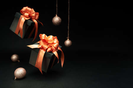 Falling gift boxes with orange ribbon, balls with copy space. Xmas present, Christmas banner, Horizontal christmas poster, greeting cards, headers, website.