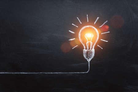 idea concept with innovation and inspiration, style symbol of creativity, brainstorm, creative idea, thinking. Lightbulb drawed by chalk representing ideas on dark background. 版權商用圖片