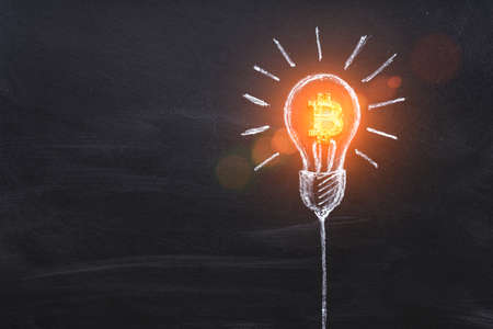 Bitcoin business idea. Cryptocurrency symbol in light bulb. Creativity, thinking. Lightbulb drawed by chalk representing generating ideas for business on dark background.
