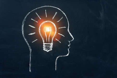 Idea concept with innovation and inspiration, style symbol of creativity, brainstorm, creative idea, thinking. Lightbulb in head of businessman drawed by chalk representing ideas on dark background.