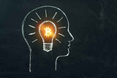 Bitcoin business idea. Cryptocurrency symbol in light bulb in head of businessman. Creativity, thinking, drawed by chalk representing generating ideas for business on dark background.