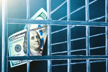 100 US dollar bill in prison. Investment trap, boycott currency concept. The concept of penalty for money laundering, theft, crime and the penalty for tax evasion. Corruption and counterfeiting