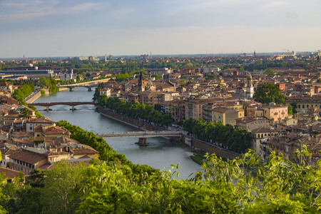 Bridges on the Adige River in Verona, Italy. Bright urban landscape with bridges, roofs and towers. View from above.