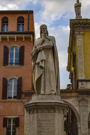 Monument to Dante Alighieri in Piazza dei Signori in Verona. Sunlight is an enlightening statue of Dante Alighieri holding his chin. Редакционное