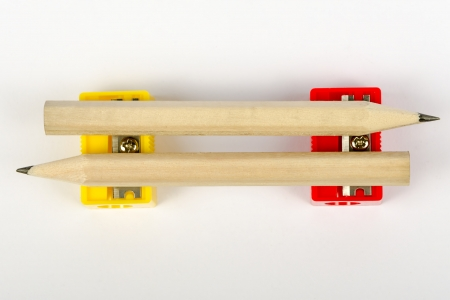 Two wooden pencils with sharpeners red and yellow on a white background
