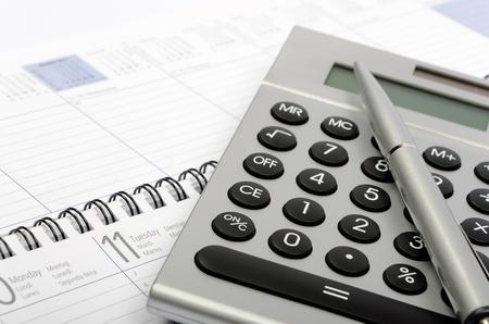 A metallic calculator, a metallic pen and organizer background Stock Photo