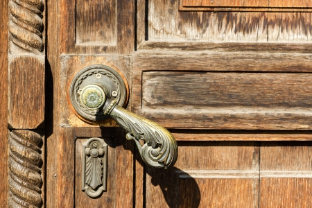Vintage wooden door with a ornamental metal handle photo