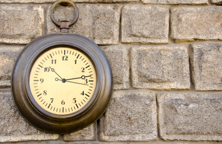 Retro metal clock on a stone wall