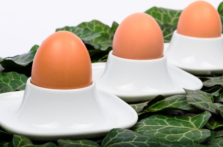 egg cups: Three eggs and egg cups on a green background Stock Photo
