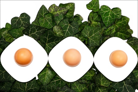 Three eggs and egg cups on a green background Stock Photo