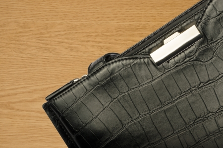 A black business bag on a wooden background