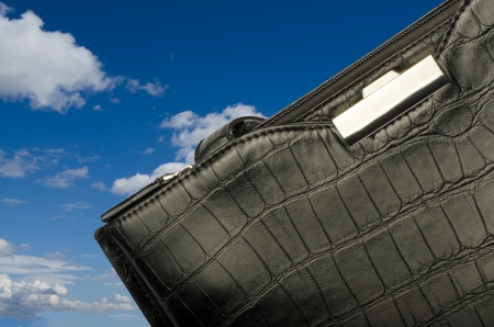 A black business bag on background of sky and clouds Stock Photo - 18640786