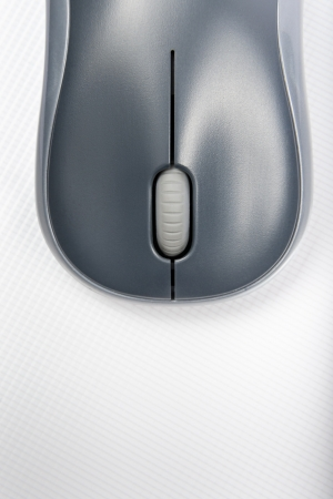 A wireless mouse positioned vertically on the cover of a laptop photo