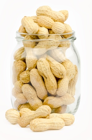 A jar full of unpeeled peanuts on a white background