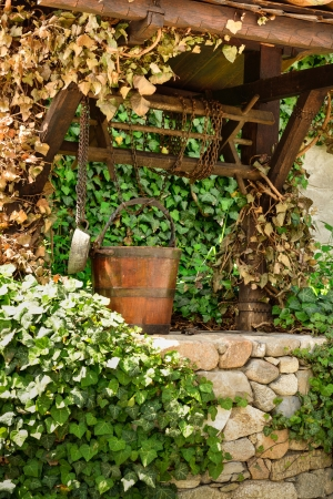 Old water well and a wooden bucket in the garden photo