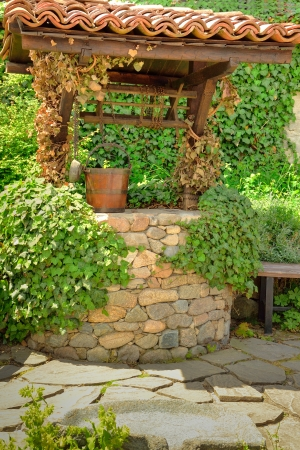 Old water well and a wooden bucket in the garden Stock Photo - 20165908