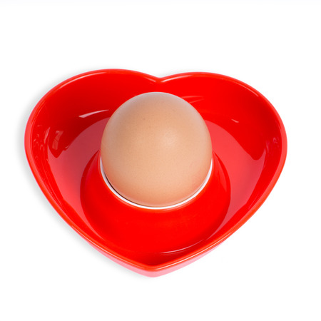 Isolated egg in a red heart-shaped eggcup on a white background