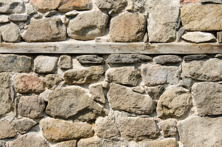 Wall of crushed stone, masonry and wooden plank photo
