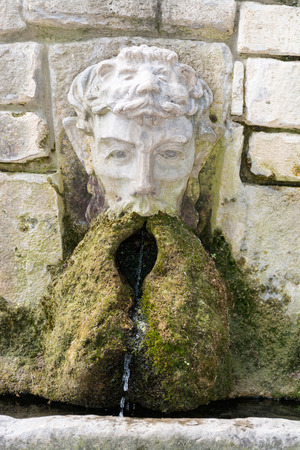 Stone wall fountain with green moss, Balchik, Bulgaria